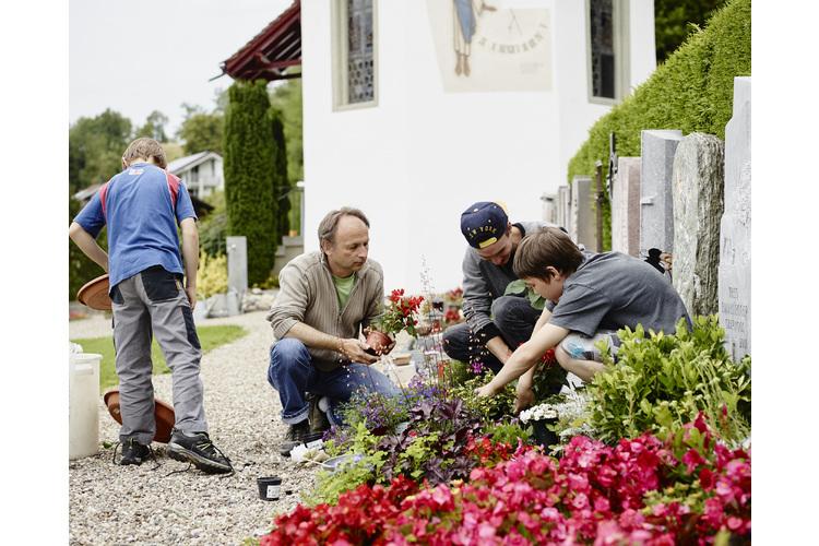 Erich Gisi mit seinen Buben auf dem Friedhof. Das Grab pflegt die Familie zusammen.