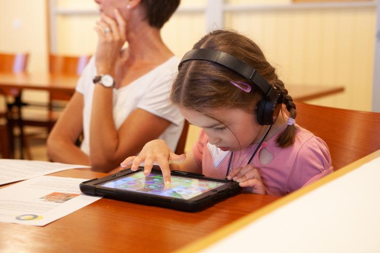 Milla beschäftigt sich mit ihren Lern-Apps, während ihre Mutter am Dravet-Treffen teilnimmt.